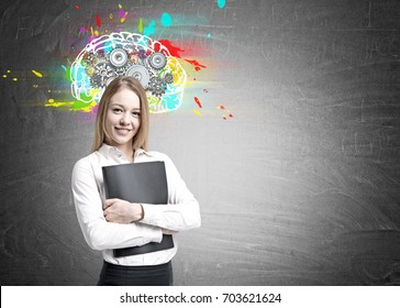 Smiling blonde businesswoman wearing a white blouse is hugging a folder and standing near a blackboard with a colorful brain sketch and gears on it. Mock up