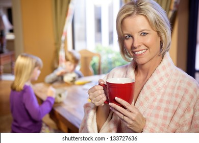 Smiling blonde Caucasian mother in foreground with her two children at the breakfast table in the kitchen, eating meal in the morning