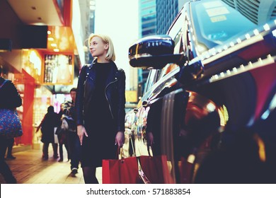 Smiling blonde female shopper dressed in trendy outfit waiting for customer ready to make  purchases in stylish stores of Chinese designers located in huge luxury building of mall standing outdoors
