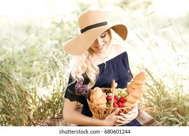 Smiling blonde girl 22-24 year old having picnic in park. Posing outdoors. Summer season. 20s.