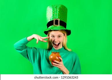 Smiling blonde girl in Leprechaun costume holds pot with gold. Green hat. Leprechaun. Pot with gold. Green leprechaun. Hat with clover. Saint Patrick's Day. Irish Traditions. Saint Patrick.