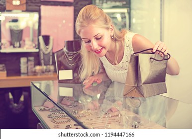 smiling blonde girl looking at accessorizes and bijouterie at glass showcase in store