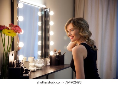 Smiling blonde girl primp at the mirror with lamps in the beauty studio. A happy satisfied customer of make-up and hairstyle service. Beautiful face with natural makeup and luxurious curls.