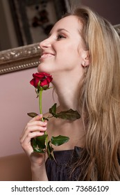 Smiling blonde girl with a red rose
