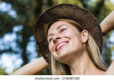 Smiling blonde girl wearing hat on warm summer day