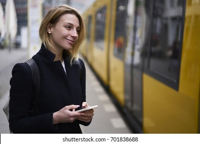 Smiling blonde hipster girl satisfied with getting into tramway monitoring traffic schedule via application installed on smartphone, attractive female tourist paying for bus online using 4g connection