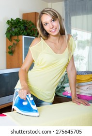 Smiling blonde housewife ironing at ironing board in home