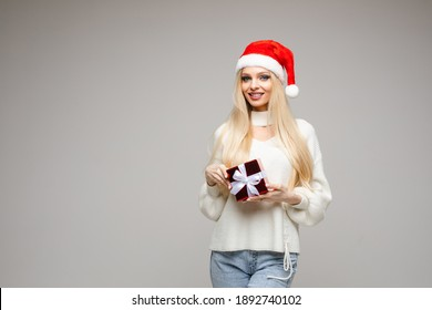 Smiling blonde lady holding small present box in studio