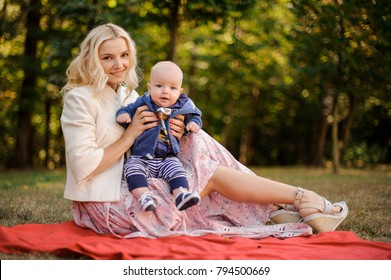 Smiling blonde mother with a baby son sitting on the blanket in a beautiful autumn park