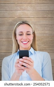 Smiling blonde sending a text message against wooden planks