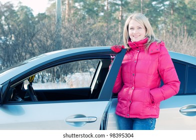 Smiling blonde standing by the car outdoors and looking at camera