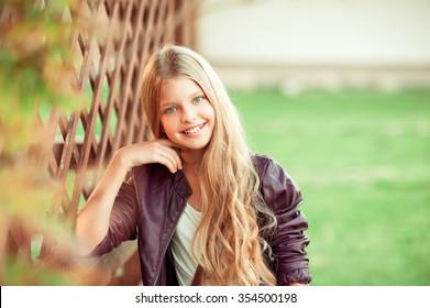 Smiling blonde teen girl 12-14 year old posing outdoors. Looking at camera.