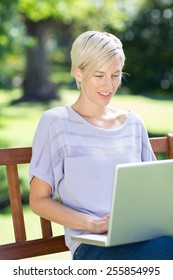Smiling blonde using laptop in a park on a sunny day