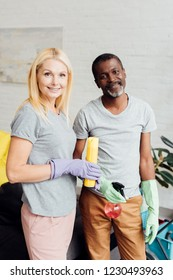 smiling blonde woman and african american man in rubber gloves holding housecleaning equipment