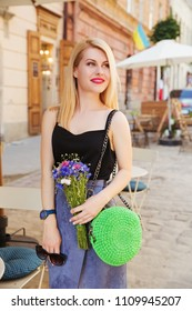 Smiling blonde woman with bright green knitted handbag. Stylish woman in black top and blue suede skirt with cornflower bouquet in hand. Street look, casual fashion concept