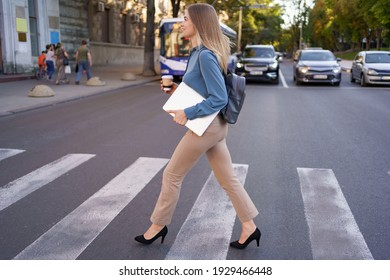Smiling blonde woman crossing zebra with coffee and laptop