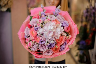 Smiling blonde woman with a large and colorful bouquet of beautiful pink and purple flowers in the room