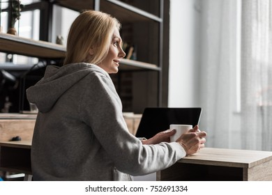 smiling blonde woman looking away while drinking coffee and using laptop at home