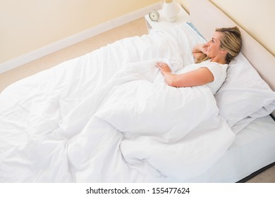 Smiling blonde woman lying on her bed in her bedroom