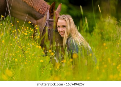 Smiling blonde woman sitting in the meadow with her arabian horse