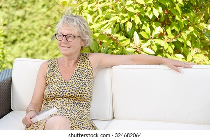 smiling blonde woman sitting on the sofa , in a garden