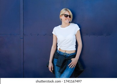 smiling blonde woman with sunglasses and white tee against blue metal background in city summer day t shirt mock up