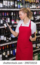 Smiling blonde worker looking at a wine bottle in supermarket