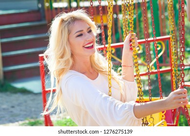 smiling blonde young elegant woman portrait  in amusement pak on flying carousel summer day close