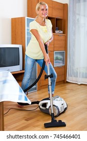 Smiling blonde young woman hoovering in living room