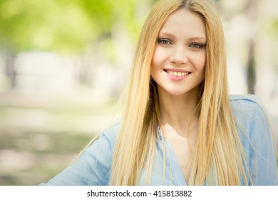 smiling blonde young woman portrait in a green cityscape