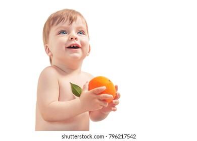 Smiling blue-eyed baby boy holding an orange on a white background. Isolated