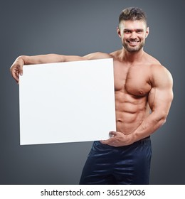 Smiling bodybuilder holding blank white poster isolated on gray background. Handsome muscular man holding white board in hands.