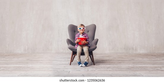 Smiling boy in 3d glasses with popcorn at home