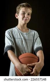 Smiling boy, age 11, holding basketball