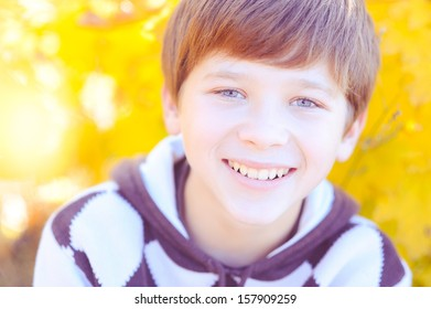 Smiling boy at autumn yellow background outdoors
