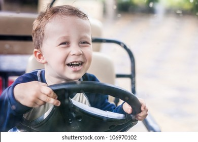 Smiling boy behind the wheel of the electric vehicle