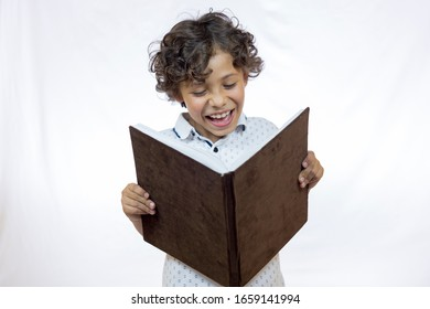Smiling boy between 8 and 9 years old holding a book while reading it and standing against white background