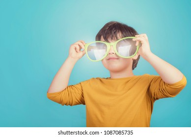 smiling boy with big sunglasses on blue background