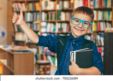 Smiling boy with blue glasses frame, tie, backpack and a stack of books showing the cool sign with his arm on a book background in. the library. Education, Knowledge, getting ready to school.