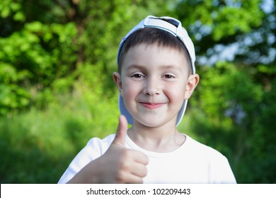 smiling boy in blue hat and white t-shirt holding thumb-up