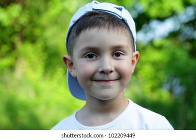 smiling boy in blue hat and white t-shirt
