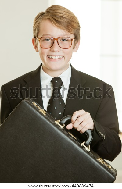 Smiling boy in business suit holding brief case wearing polka dot tie and glasses