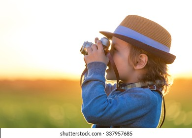 Smiling boy with a camera in the field