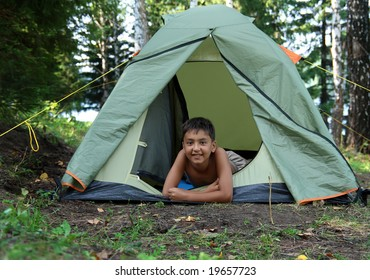 smiling boy in camping tent in forest
