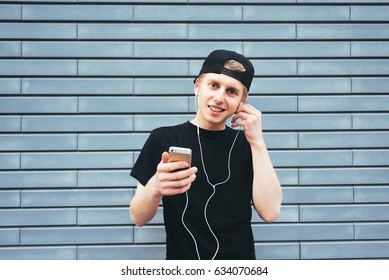 Smiling boy in a cap and T-shirt listening to music on headphones with the phone on the background wall in blue. A young man enjoying the music.