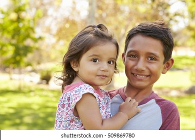 Smiling boy carrying his little sister looks to camera