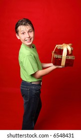 A smiling boy in casual clothes carrying gifts tied with ribbon