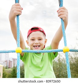 Smiling boy in casual hanging on ropes outdoors