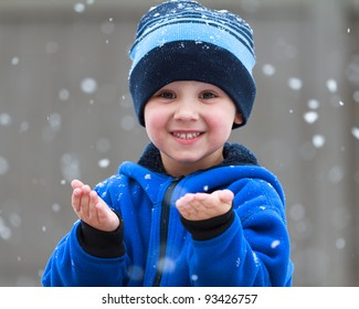smiling boy catching snowflakes