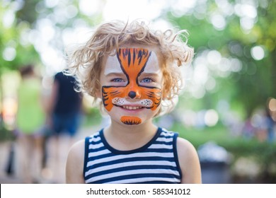 smiling boy with curly hair and face art paintibng like tiger or leopard